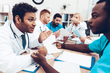 Doctors Meeting. Diagnostic Discussion. Multinational Medicals. Professional Consultation. Patients Test Results. Young Specialists. Clinician Team Group. Physician Assistants. Sitting Interns. Stock Photo