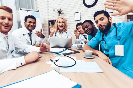 Multinational Doctors Meeting. Resting Concept. Medical Office. Cups Of Tea. Coffee Break. Cheerful Medicians Saying Hello. Working Together. Teamwork Connection. Hospital Team Talk.