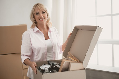 Portrait of Mature Woman near Opened Box with Things Folded in Package. Preparation for Moving to New Place of Residence. Packed Household Goods for Moving into New House. New Apartment Concept.