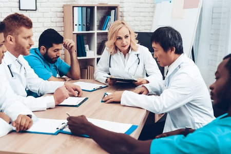 Doctors Meeting. Diagnostic Discussion. Multinational Medicals. Professional Consultation. Patients Test Results. Young Specialists. Clinician Team Group. Sitting Interns. Surgeon Assistants. Stock Photo