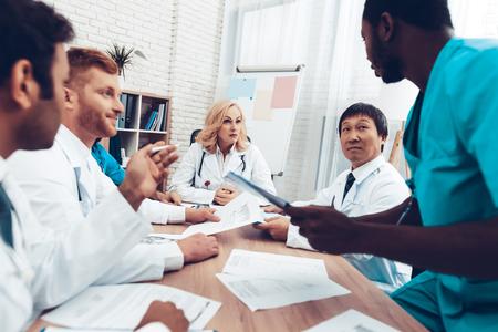 医師会議。診断ディスカッション。多国籍医療.専門的な相談。患者の検査結果。若いスペシャリスト。臨床医チームグループ。医師のアシスタント。インターンに座る。 写真素材 - 105914697