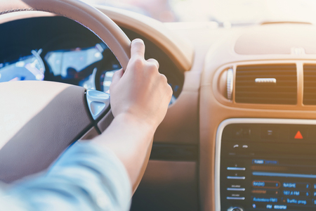 Close Up. Girl Drives Car with Hand Behind Wheel. Kind of Arm and Salon. Lifestyle Concept. Travel Concept. Summer Vacation Concept. Time to Relax Concept. Car Passenger. Beautiful Teens in Vehicle.