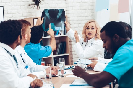 Multinational Doctors Duscussing. Patients Pelvis X-ray. Group Specialist Connection Interacting. Hospital Diagnostic Meeting. Medical Results. Clinician Team Group. Physician Assistants.