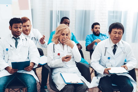 Multinational Doctors Yawning. Office Meeting. Bored Specialists. Hospital Discussion. Medical Teamwork Connection. Diagnostic Question. Clinician Team Group. Professional Team Talk.