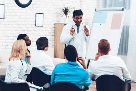Indian Doctor Shares Experience With Colleagues. Paper Desk Information. Professional Medical Consultation. Multinational Medician Meeting. Teamwork Connection. Clinician Team Group. Stock Photo