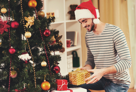Attractive Man Under Cristmas Tree. Young Male Dressed in Santa Hat. Xmas Tree. Preparations for Holiday. Preparations for Celebration. Holiday Concept. Caucasian Young Man. Christmas Present.