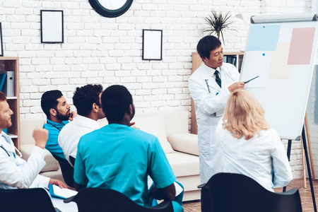 Asian Doctor Shares Experience With Colleagues. Paper Desk Information. Professional Medical Consultation. Multinational Medician Meeting. Teamwork Connection. Clinician Team Group.