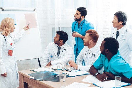 Multinational Medician Consultation. Head Doctor Discussing. Information On Paper Desk. Medical Teamwork Connection. Clinician Team Group. Hospital Diagnostic Meeting. Physician Assistants.
