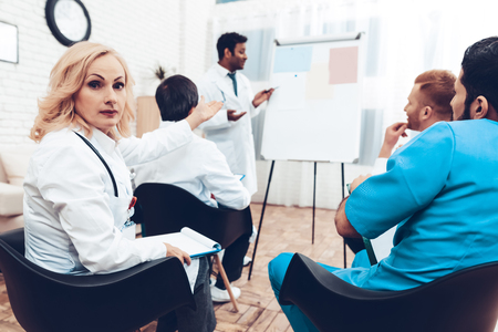 A female doctor looks at the camera while another doctor shares his experience during a medical meeting. In the office, doctors of different nationalities sit. On the white board hang sheets of paper.