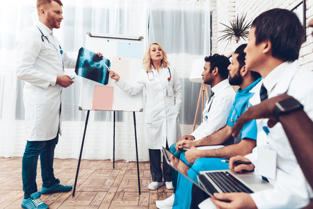 Team Analysis. X-ray Results Paper Desk Information. Professional Medical Consultation. Multinational Medician Meeting. Teamwork Connection. Clinician Team Group. Diagnostic Discussion.