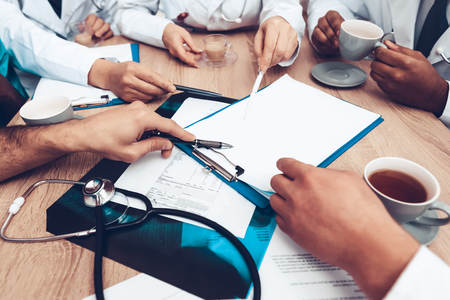 Professional Consultation. Hospital Workers. Documents Rewiew. Multinational Doctors Hands Concept. Paper Desk Blank. Diagnostic Discussion. Clinician Team Group. Physician Assistants.