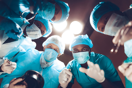 Doctors Staring On Patient. Operating Table Look. Preparing To Surgery. Clinician Team Group. Under The Light. Working Together. Teamwork Connection. Holding A Scalpel. Medicine In Masks.