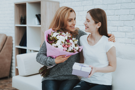 Smiling Daughter Gives Mother Flowers and Gift. Relationship in Family. Holiday at Home. Happy Mother. Friendly Relations. Celebrating Together. Happiness in Family Concept. Presenting Gift.