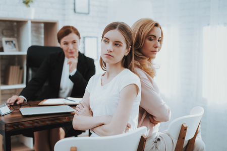 Mother and Young Daughter in Psychologist Office. Visit to Doctor. Conflict in Family. Parent and Child. Unhappy Woman. Communication Concept. Relationship Concept. Psychotherapy Concept. Stock Photo