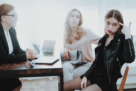 Upset Teenage Daughter in Jacket in Psychologist Office with Mother. Punk in Lather Jacket. Communication Concept. Psychotherapy Concept. Puberty Problems. Conflict in Family. Family Doctor. Stock Photo
