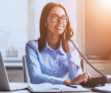 Young Business Lady Talking on Phone and Smiling while Working in Office. Work in Call Center. Income and Outcome Calls. Work and Job Concepts. Smiling Woman. Using Talk in Office. Business Concept.