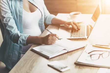 Close up. Pregnant Woman Working on Laptop. Holding Pen and Smiling while Working at Home. Young Freelancing Mother. Freelancing at Home. Remote Work Concepts. Pregnant Businesswoman.