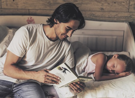 Caring Father Reading Book to Small Daughter Before Bed. Girl Falling Asleep. Happy Family Concept. Spending Time Together. Family Communication. Parent and Happy Child. Sleeping in Bed.