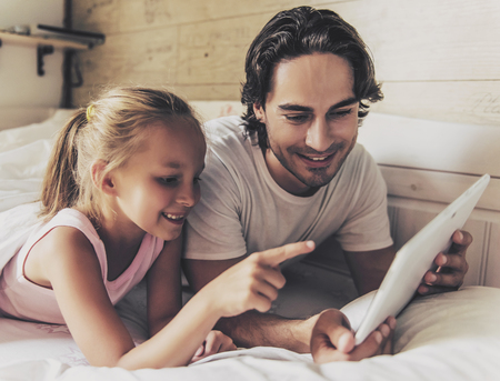 Father and Small Daughter Using Digital Tablet and Smiling. Lying on Sofa. Web Surfing. Watching Video. Studying at Home Concept. Happy Family Concept. Relaxing at Home. Girl with Digital Device.