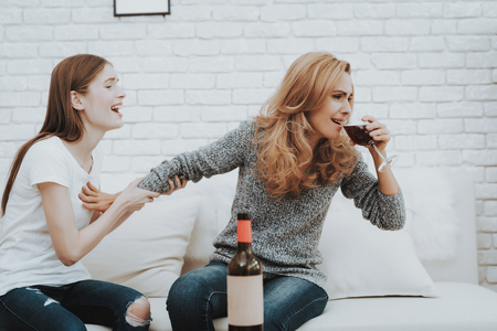 Upset Screaming Daughter with Drunk Mother at Home. Relationship in Family. Worried Girl. Psychological Help. Screaming Girl. Support Concept. Addicted to Alcohol. Women on White Sofa. Banco de Imagens