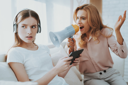 Quarrel between Mother and Daughter in White Room. Emotional Discussion. Sitting on Couch. Conflict in Family. Parent and Child. Unhappy Girl. Communication Concept. Relationship Problem.