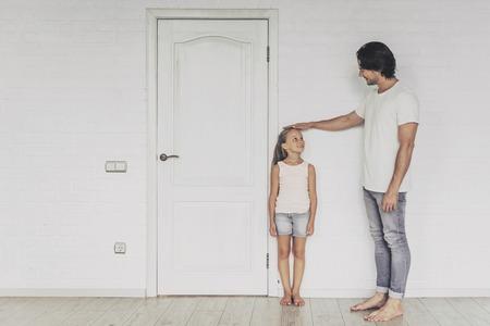 Lachende vader meten hoogte van schattige dochter in de buurt van deur thuis. Beiden kijken elkaar aan. Gelukkig familieconcept. Samen tijd doorbrengen. Familiecommunicatie. Ouder en gelukkig kind.