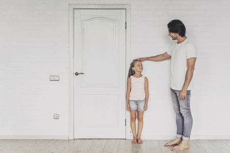 Smiling Father Measuring Height of Cute Daughter near Door at Home. Both Looking each other. Happy Family Concept. Spending Time Together. Family Communication. Parent and Happy Child.