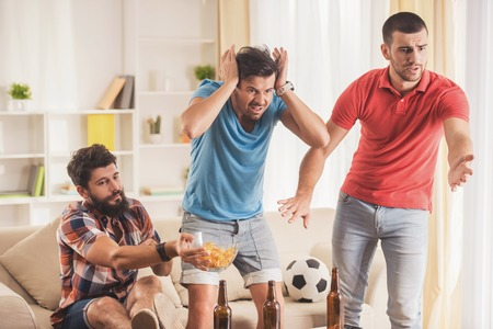 Upset Men with Beer Watching Football at Home. Friends on Party. Weekend at Home. Three Happy Friends. Communication with Friends Concepts. Drinking Beer in Bottle. Football Fans. Soccer Concept. Banco de Imagens