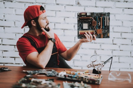 Young Man in Red Cap with Broken Motherboards in Workshop. Modern Workshop Concept. Manufacturing Instrument. Modern Tools Concept. Electronic Devices Concept. Mobile Device Hardware. Wooden Desk. Фото со стока