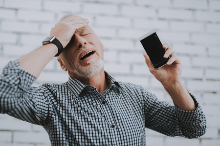 Old Man with Broken Mobile Phone Holding Head. Electronic Devices Concept. Mobile Device Hardware. Man with Gray Hair. Upset Man. Broken Digital Device. Disappointed Man. White Room.