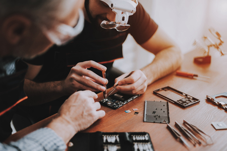 Two Men Repairing Hardware Equipment in Workshop. Repair Shop. Young and Old Workers. Digital Device. Man in Glasses. Electronic Devices Concept. Mobile Device Hardware. Workers with Tools.