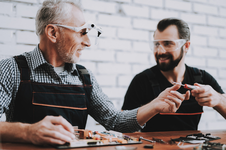 Two Men Repairing Hardware Equipment in Workshop. Repair Shop. Worker with Tools. Computer Hardware. Young and Old Workers. Modern Devices. Digital Device. Laptop on Desk. Electronic Devices Concept.