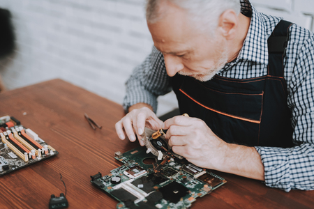 Bearded Old Man Repairing Motherboard from PC. Repair Shop. Worker with Tools. Computer Hardware. Magnifying Glass. Soldering Iron. Digital Device. Laptop on Desk. Electronic Devices Concept.