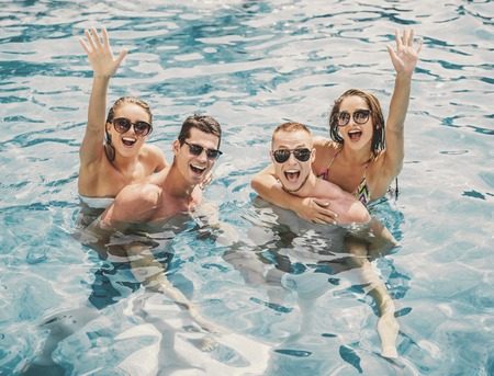 Beautiful Young People Having Fun in Swimming Pool. Leisure in Summer. Vacation in Summer. Recreation Concepts. Boyfriends and Girlfriends. Vacation for Couple. People in Swimsuits. Stockfoto