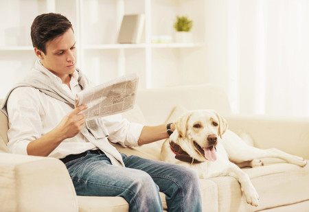 Young Man Sitting on White Sofa with Dog at Home. Reading Newspaper. Rest at Home. Relaxation Concept. People and Pets. Relaxed Man. White Dog. Puppy in Room. Man with Newspaper.