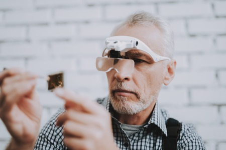 Elderly Man with Special Glasses in Repair Shop. Worker with Tools. Magnifying Glass. Worker in Glasses. Worker in Black Uniform. Man with Gray Hair. Modern Workshop Concept. Engineer in Uniform. Foto de archivo