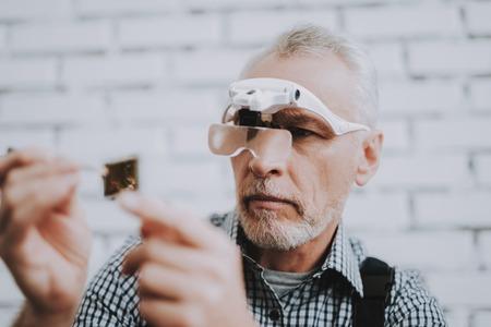 Elderly Man with Special Glasses in Repair Shop. Worker with Tools. Magnifying Glass. Worker in Glasses. Worker in Black Uniform. Man with Gray Hair. Modern Workshop Concept. Engineer in Uniform. Zdjęcie Seryjne