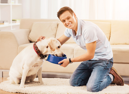 Young Man Feeding Dog Sitting on Floor in Room. est at Home. Relaxation Concepts. People and Pets. Relaxed Man. White Dog. Puppy in Room. Man near Sofa. Smiling Man. Domestic Life. Stock Photo