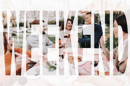 Young People Are Drinking On Holiday Vacation. Smiling Friends Are Having Fun. Sweater Weather. Sunny Day. Nature Relaxing. Holiday Company Meeting. Resting Together. Grill Liesure. Stock Photo