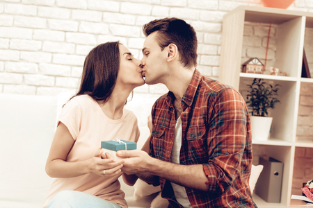 Guy Makes A Gift To Girlfriend On Valentines Day. Love Each Other. Sweethearts Holiday Concept. Young And Handsome. Happy Relationship. Feelings Showing. Romantic Kiss. Celebrating Date.