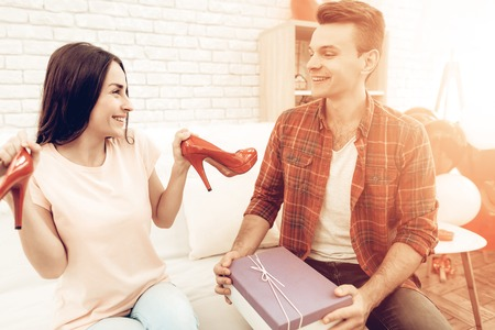 Guy Makes A Gift To Girlfriend On Valentines Day. Love Each Other. Sweethearts Romantic Holiday Concept. Young And Handsome. Happy Relationship. Feelings Showing. Present Opening. Stock Photo