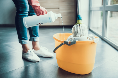 Woman in Gloves prepearing to Wipe Floor with Mop. Closeup of Girl wearing Protective Gloves mixing Cleaning products with water in Bucket with Mop. Woman Cleaning Apartment