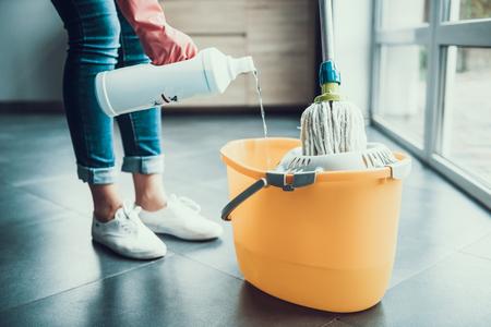 Vrouw in handschoenen die zich voorbereiden om de vloer met een zwabber af te vegen. Close-up van meisje het dragen van beschermende handschoenen reinigingsproducten mengen met water in emmer met dweil. Vrouw schoonmaak appartement