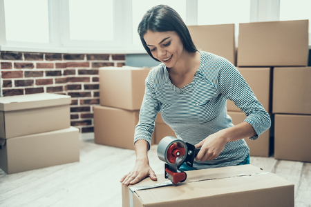 Young Smiling Woman Packing Cardboard Box at Home. Happy Beautiful Girl Preparing to Relocation by Packing Carton Boxes with Scotch Tape. Young Girl Moving to new Apartment