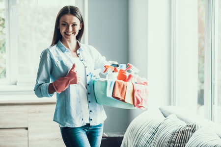 Young Happy Woman holds Cleaning Equipment at Home. Beautifull Smiling Girl wearing Gloves holding Cleaning Supplies ready to start Cleaning Apartment. Woman preparing to Clean