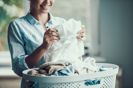 Young Beautiful Smiling Woman holds Clean Clothes. Closeup of Happy Beautiful Girl holding Fresh Clothing just after Laundry. Young Attractive Woman doing Housework. House laundry Stock Photo