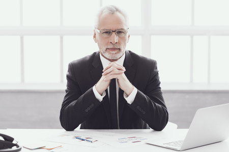 Geschäftsmann bei der Arbeit im Büro. Unternehmenslebensstil. Professioneller reifer bärtiger Arbeiter, der am Schreibtisch neben Laptop sitzt. Erfolgreicher selbstbewusster Geschäftsmann, der Anzug und Brille bei der Arbeit trägt. Standard-Bild - 107271715