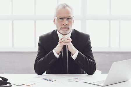 Geschäftsmann bei der Arbeit im Büro. Unternehmenslebensstil. Professioneller reifer bärtiger Arbeiter, der am Schreibtisch neben Laptop sitzt. Erfolgreicher selbstbewusster Geschäftsmann, der Anzug und Brille bei der Arbeit trägt.