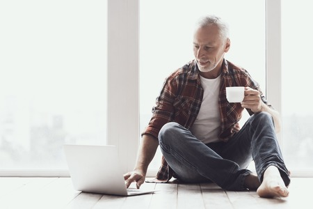 Smiling Mature Man with Beard Using Laptop at Home. Casual Happy Adult Man Sitting on floor and drinking Coffe while using Laptop. Handsome Aged Man wearing Glasses Relaxing at Home