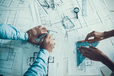 Close-up van handen van architecten Blauwdruk tekenen. Twee creatieve collega's ontwerpen plan van nieuw gebouw samen in kantoor. Bedrijfsmensen die samenwerken. Teamwerk Concept Stockfoto